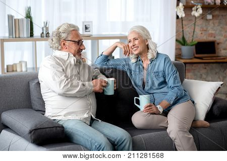 Happy mature husband and wife are drinking coffee together at home. They are sitting on sofa and talking while laughing
