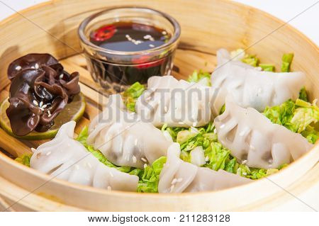 Close Up Various Dim Sum And Sauce In Bamboo Steamer On The White Background Isolated. Chinese Cuisi