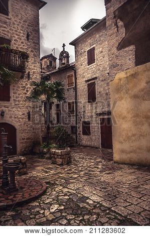 Medieval vintage street with old buildings with wooden shutters and stone pavers with medieval architecture in old european city Kotor in Montenegro