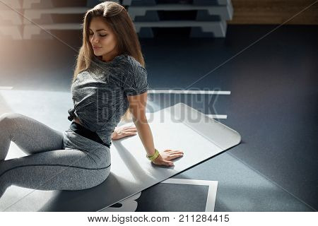 Fit adult woman resting in gym after a hard workout. Long haired caucasian coach sitting on yoga mat. Fitness concept.