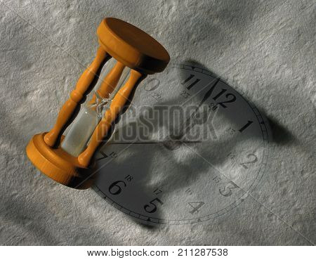 SAND TIMER CASTING SHADOW ON CLOCK FACE