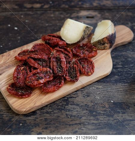 cheese on a wooden board made of olive wood with dried tomatoes
