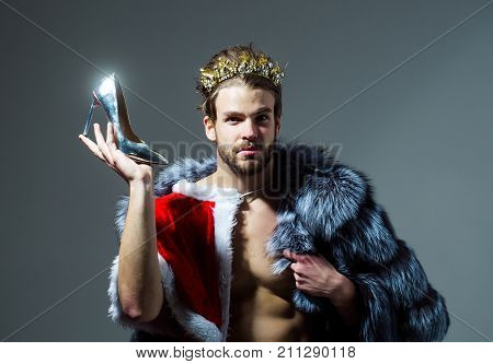 Drag queen homosexual and trans. Freak gay and transvestite. Cinderella prince with shoe on grey background. Freedom and lgbt kitsch. Christmas guy in santa fur coat in crown.