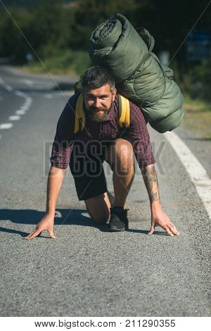Man traveler smile with backpack on start position to run on road. Health and active lifestyle. Ready steady go. Summer vacation travel concept.