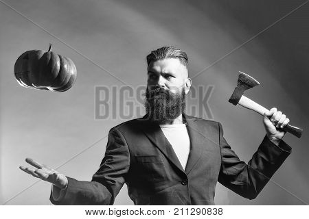 Handsome young man with long beard and moustache in black jacket holding halloween pumpkin and axe in studio on grey background