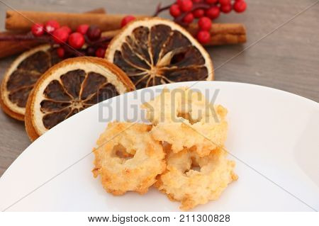 Plain traditional christmas (Xmas) festive decoration background with white plate on wooden background with dried orange holly branch cinnamon and special coconut christmas sweets on plate (Czech homemade x-mas cookies)
