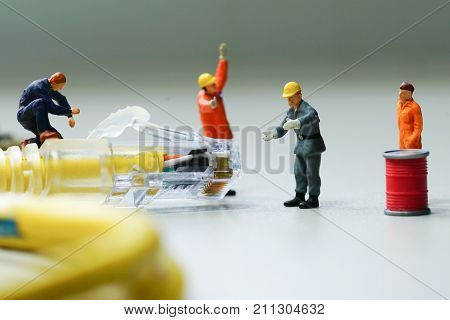 Technicians try to repair cable wire network. Miniature people.