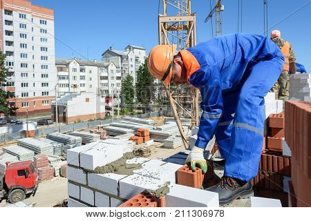Yoshkar-Ola, Russia - June 08, 2015 Bricklayer puts a wall of a multi-storey building made of white brick