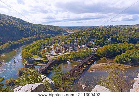 Harpers Ferry historic town and National Park as seen from a high mountain point. Harpers Ferry autumn panorama with railroad bridges across Shenandoah and Potomac rivers.