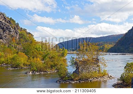 Shenandoah River with old bridge remains in Harpers Ferry West Virginia USA. Blue Ridge Mountain in Harpers Ferry National Historical Park in autumn.
