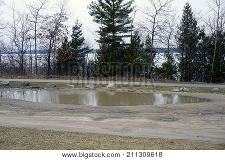 Melted snow forms a large puddle in the public parking lot at the Tannery Creek Trailhead, near Bay View, Michigan, during March.