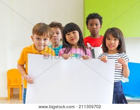 Diversity children holding blank poster in classroom at kindergarten preschoolMultiethnic Group with sign boardmock up for adding text or design.
