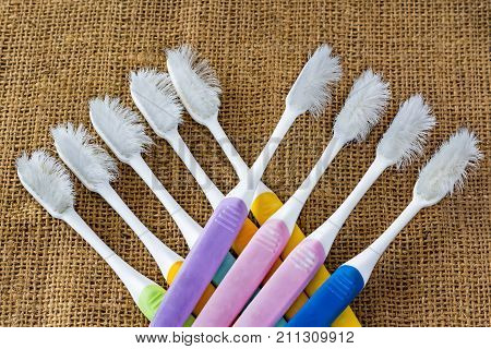 Several toothbrushes dilapidated placed on a brown sackcloth. Dental Care Concept.