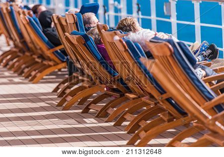 Sea Travel and Cruise Ship Relax. People Relaxing on Deckchairs During Transatlantic Cruise.