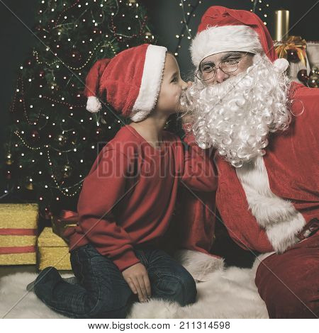 Image of happy Santa Claus and boy near the decorated Christmas tree. Wishes list
