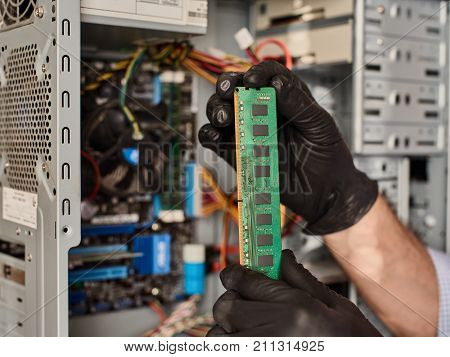 Close up of male hands in gloves installing ram Memory card