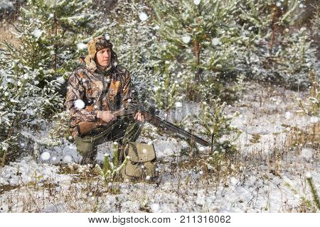 Hunter with a backpack and a hunting gun in the winter forest. Man is charging a hunting rifle. Winter snow-covered forest.