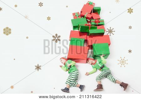 Funny two boys dressed in Santas Elf costumes for Christmas, holding many gift boxes. Celebrating Christmas. Copy space at white background. Big gift box. Cristmas shopping. Merry Christmas your family.