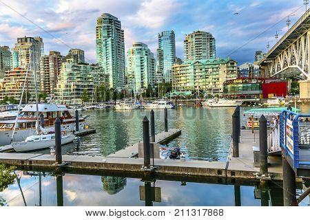 VANCOUVER, BRITISH COLUMBIA, CANADA - JULY 15, 2016 Granville Island Burrard Street Bridge Yachts Apartment Buildings Vancouver British Columbia Canada