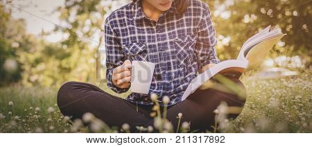 The girl sitting on a green grass with cup of coffee and reads the book young woman with coffee sitting on the grass and reading a book in the park vintage tone. banner panoramic crop for copy space. reading park. reading book. reading girl. reading coffe