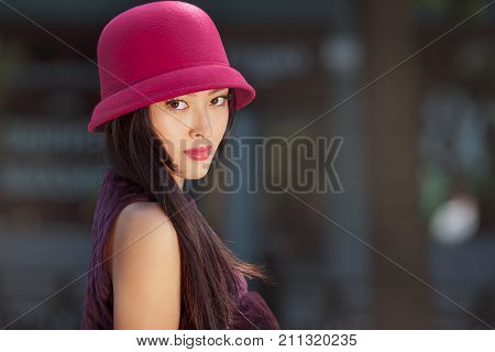 Attractive asian woman fashion portrait. Beautiful romantic mixed race asian caucasian young girl in pink hat jaket looking at camera outdoor against blurred bokeh city background. Gorgeous slim model in trendy glamour stylish clothes posing outside in ci