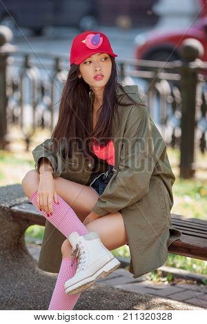 Asian woman urban fashion photo. Beautiful mixed race asian caucasian young girl in red cap green raincoat boots looking away outdoor against green blurred bokeh city background. Gorgeous slim model in trendy casual colourful clothes sitting on bench outs