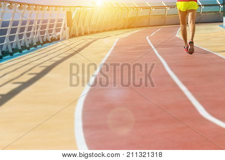 healthy vacation lifestyle. young fitness woman run on athlete running track at cruising boat. sport background