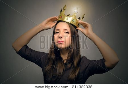Young beautiful woman holding in hands the golden crown above the head. Vip client. Premium user concept. The winner.
