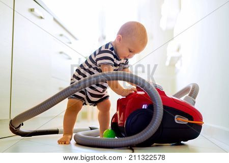 Cute baby boy with the hoover in the kitchen. Close up of a little boy playing with vacuum cleaner.