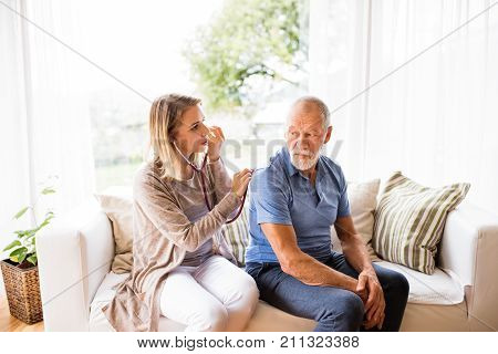 Health visitor and a senior man during home visit. A female nurse or a doctor examining a man. poster