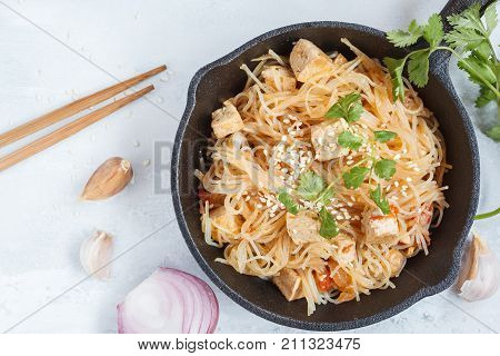 Fried vegan rice noodles with tofu and vegetables in cast iron frying pan top view light background. Healthy vegan food concept.