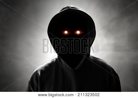 Mysterious unknown hacker standing on smoke background