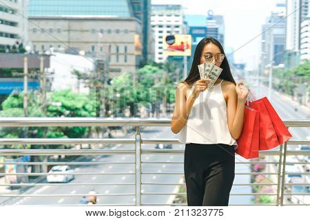 Beautiful young woman walking with many shopping bags shop and holding cash banknotes shopping summer sale and fashion at center complex bangkok.
