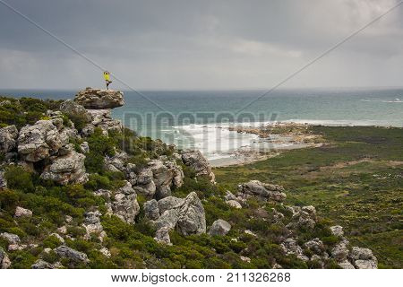 A hiker poses on top of a rocky outcrop on a trail near Cape Point, South Africa.
