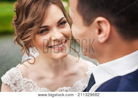 Beautiful bride and handsome groom on wedding day. Beautiful newlyweds smiling in beautiful nature near the lake. Close-up portrait