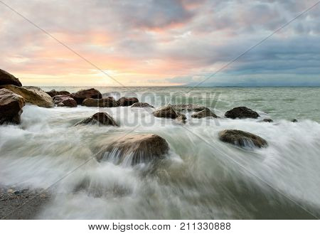 Ocean waves sunset is a surreal ocean sunset with water rushing to the shore as the sun sets on the ocean horizon.