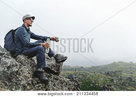 Young Traveler Man Sitting On Top And Holding Thermos In His Hand. Hiking Adventure Tourism Concept