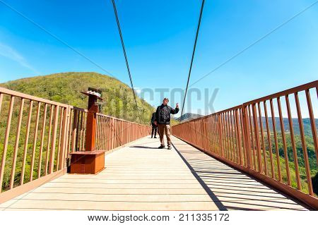 Man traveller on viewpoint terrace high up in green mountains on blue sky background. Okatse Canyon Imereti Region Georgia. Colorful summertime outdoors vertical image.