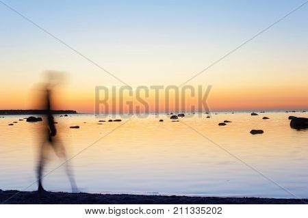 Man defocused silhouette walking on seaside water at multicolored sunset background. Long exposure. Outdoors vibrant horizontal image.