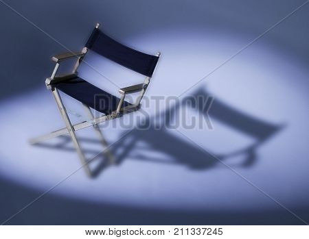 BLACK DIRECTORS CHAIR CASTING SHADOW ON WHITE BACKGROUND