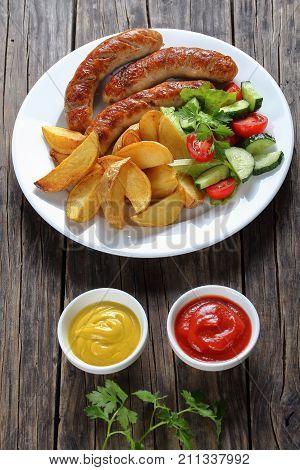 Grilled Bratwurst, Salad, Potatoes On Plate