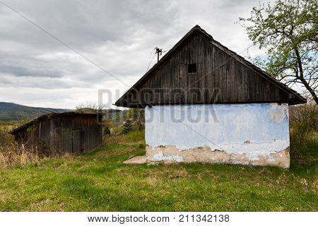 Old house with wooden roof and dilapidated wall