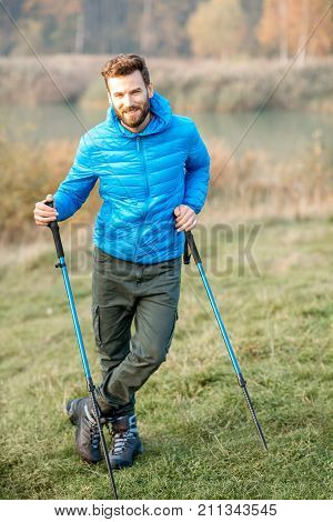 Portrait of a handsome man in blue jacket hiking with sticks outdoors near the lake and forest