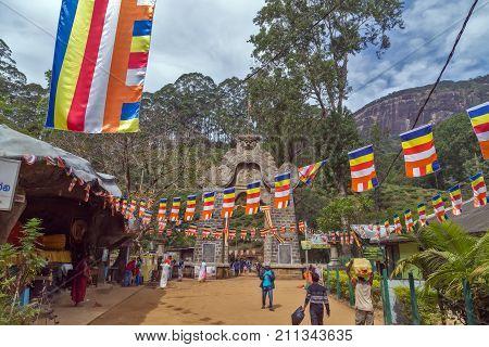 ADAM'S PEAK SRI LANKA - February 05 2016: Reclining Buddha statue at the foot of Adams Peak. Gate at the Base of SRI PADA Gateway to start of ascent ADAM PEAK Monk of the Buddhist go with pilgrims. is the most popular pilgrim place in Sri Lanka.