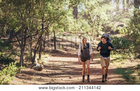 Man and woman hikers trekking on forest trail. Hiker couple exploring nature walking through the woods.