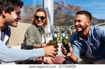 Group of friends toasting beers at a party on rooftop. Young men and woman hanging out at rooftop party and enjoying drinks.