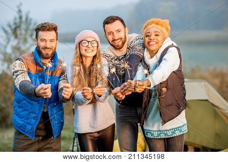 Multi ethnic group of friends dressed in sweaters celebrating with bengal fire standing together at the camping during the evening light