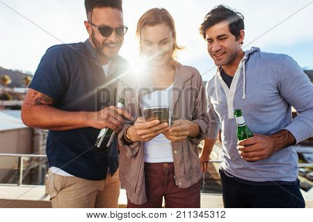 Friends At Rooftop Party Using Mobile Phone