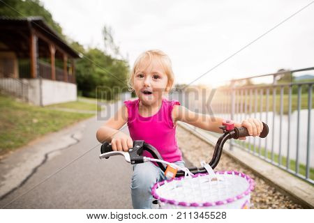 Cute little happy girl in nature by the lake, cycling and smilling. Summer time.