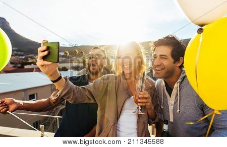 Group Of Friends Taking Selfie At Rooftop Party